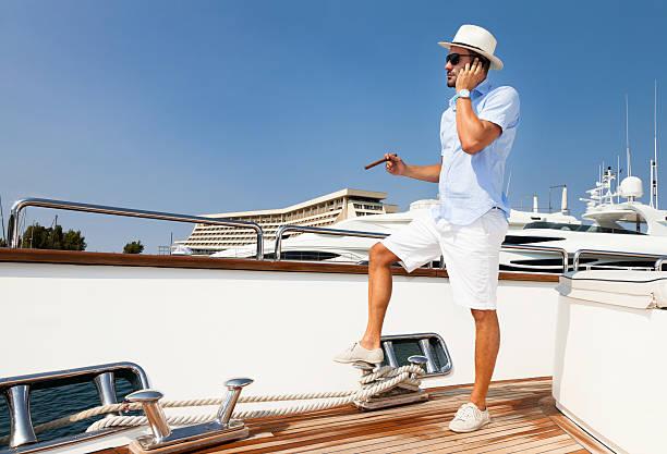 elegant businessman on board of the yacht. phone conversation. - guy with cigar stockfoto's en -beelden