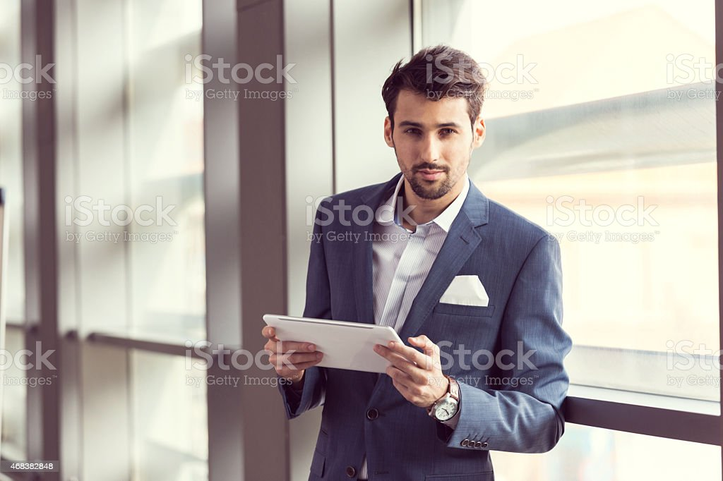 Elegant businessman using digital tablet Portrait of confident businessman wearing navy blue suit standing by the window in an office, holding a digital tablet in hands and smiling at camera. 2015 Stock Photo