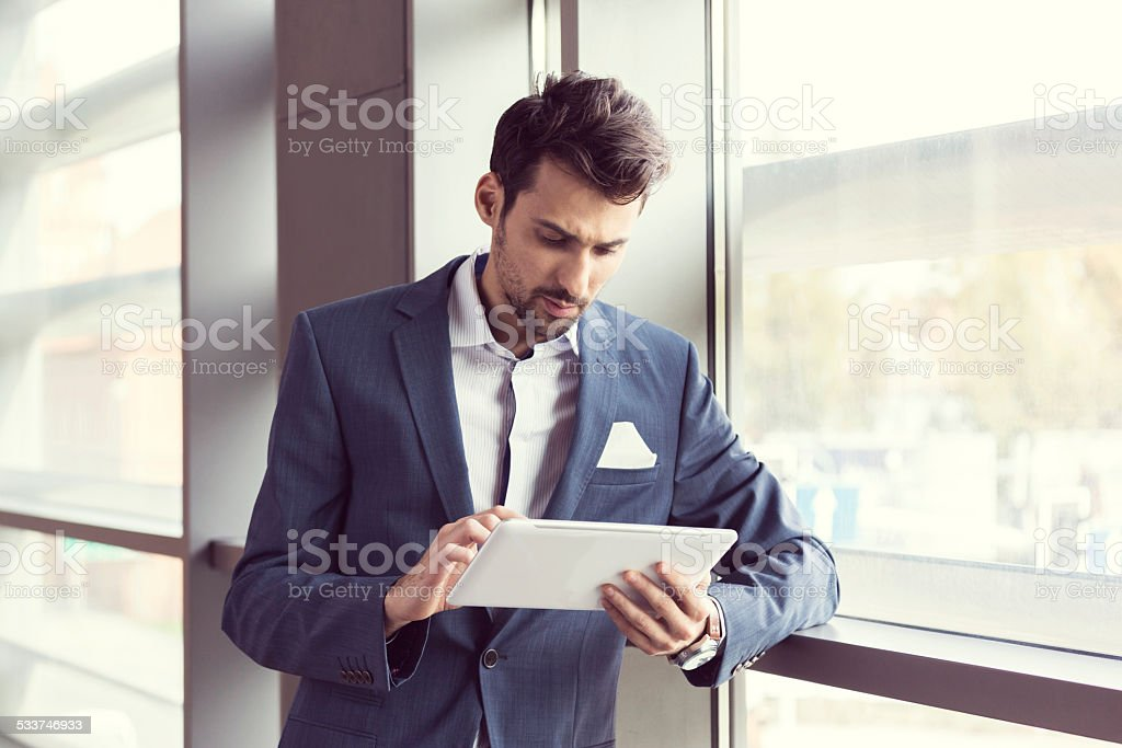 Elegant businessman using digital tablet Businessman wearing suit standing by the window in an office and using a digital tablet. 2015 Stock Photo