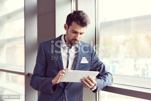 istock Elegant businessman using digital tablet 533746933
