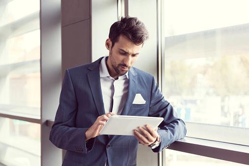 Elegant Businessman Using Digital Tablet Stock Photo - Download Image Now