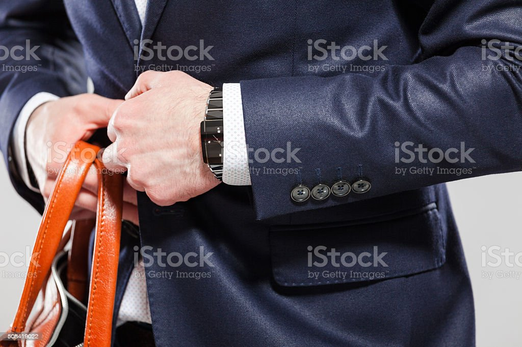 Elegant businessman wearing jacket, close up of hands Elegant businessman wearing navy blue suit, close up of hands, holding button. Unrecognizable person. Adult Stock Photo
