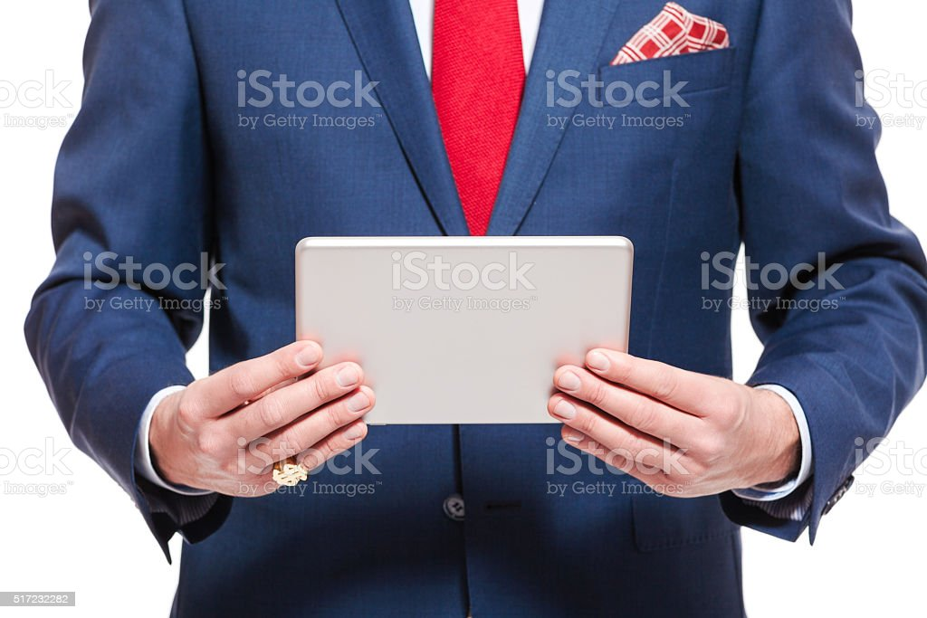 Elegant businessman wearing suit, holding a digital tablet Elegant businessman wearing suit, red tie and pocket square, holding a digital tablet. Close up of hands and torso, unrecognizable person. Studio shot, isolated on white. Adult Stock Photo