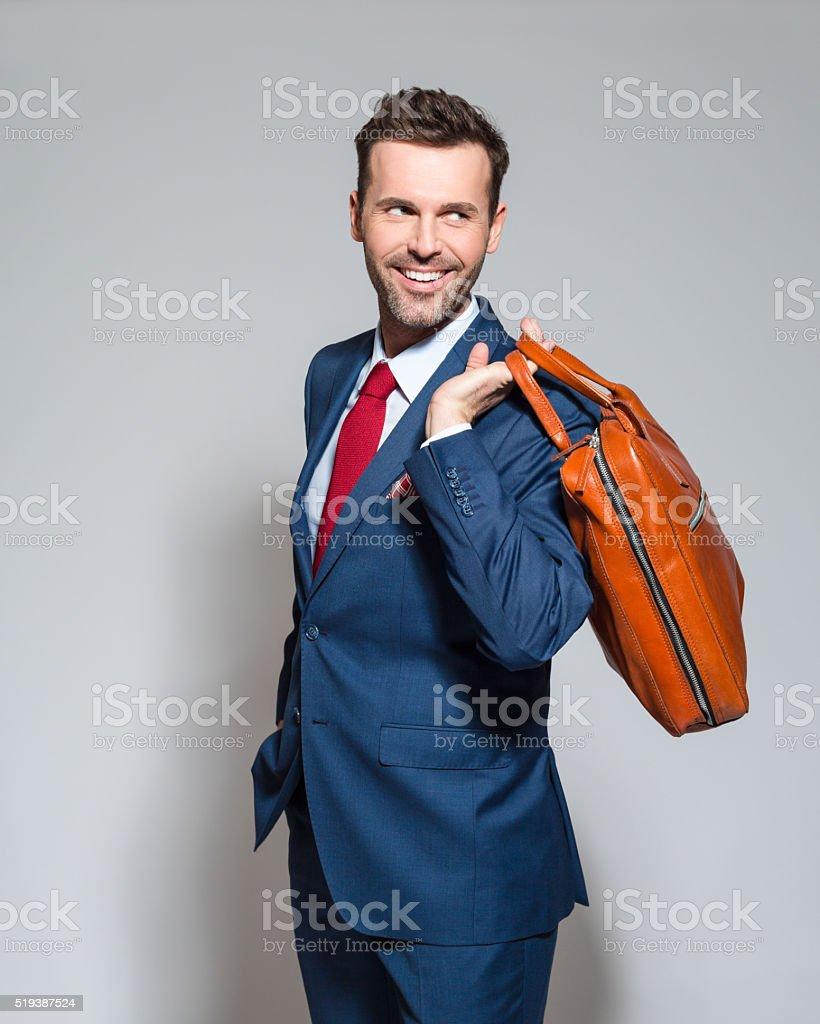 Elegant businessman wearing suit, holding briefcase Portrait of elegant businessman wearing elegant suit, holding a leather briefcase, looking away. Studio shot, one person, grey background. Adult Stock Photo