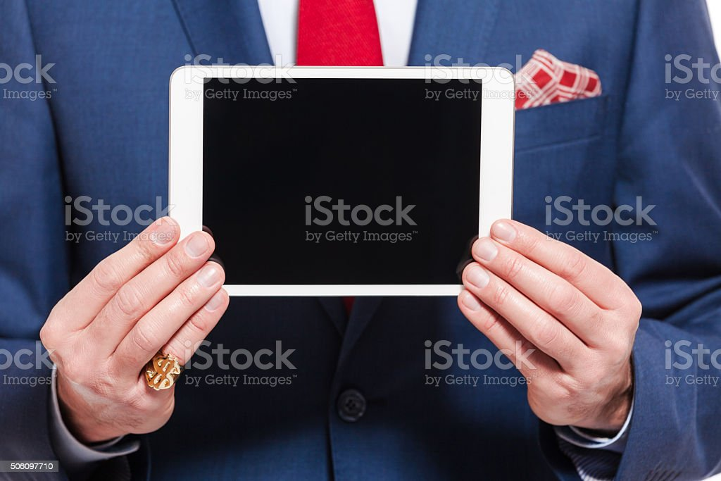 Elegant businessman wearing suit, holding digital tablet Close up of elegant businessman wearing suit, using a digital tablet. Close up of hands and torso, unregoznizable person. Adult Stock Photo