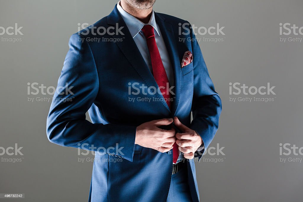 Elegant businessman wearing suit Portrait of elegant businessman wearing suit. Standing against dark grey background. Studio shot, unrecognizable person. Close up of torso. 2015 Stock Photo