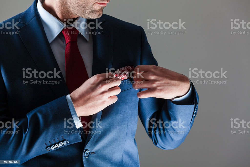 Elegant businessman wearing suit Portrait of elegant businessman wearing suit. Close up of torso, hands and cuff link. Unrecognizable person. Adult Stock Photo