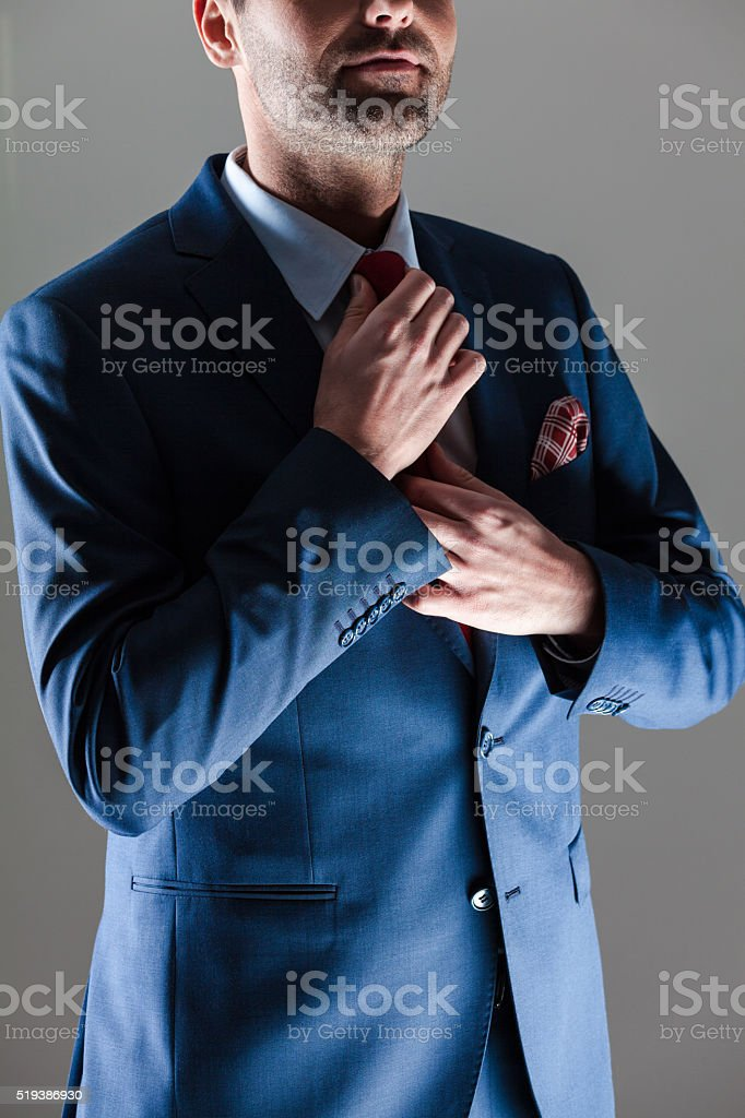 Elegant businessman wearing suit Portrait of elegant businessman wearing suit and pocket square. Standing against dark grey background. Close up of torso and hands. Adult Stock Photo