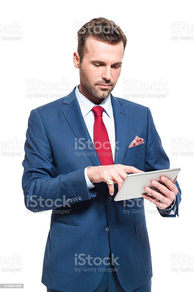 Elegant businessman wearing suit, using a digital tablet Elegant businessman wearing suit, red tie and pocket square, using a digital tablet. Studio shot, isolated on white.  Adult Stock Photo