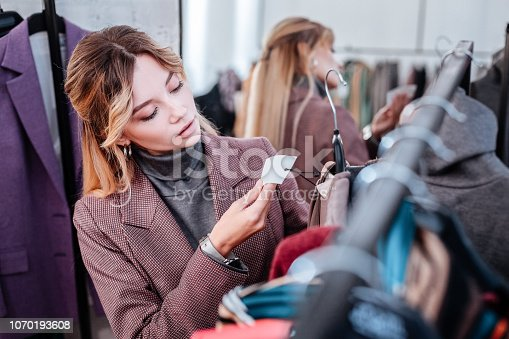 istock Elegant businesswoman shopping on weekend checking the price of dress 1070193608
