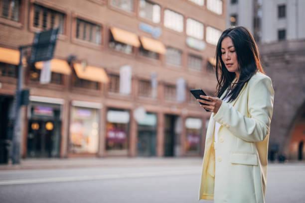 Elegant businesswoman text messaging stock photo