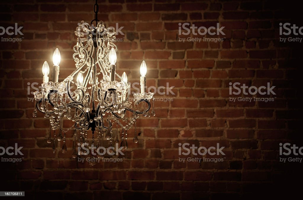 Elegant chandelier with candles in an empty brick interior stock photo
