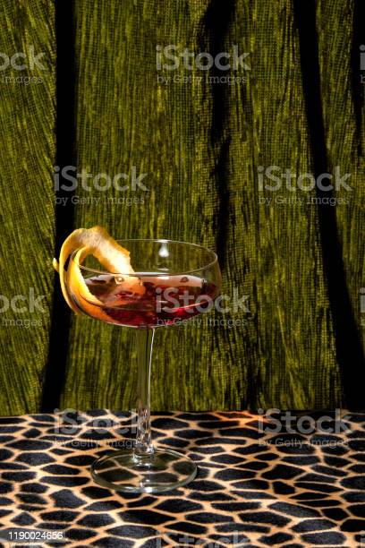 Elegant cocktail on ocelot patterned retro table top, with heavy dark green carpet behind