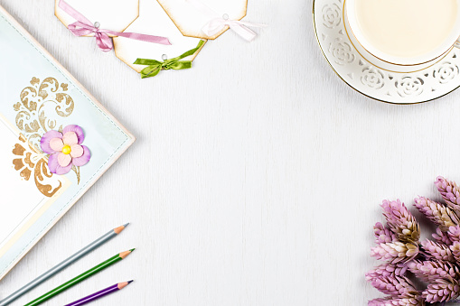Elegant coffee cup, note book, paper tags and flowers flat lay. Feminine background in pastel colors.