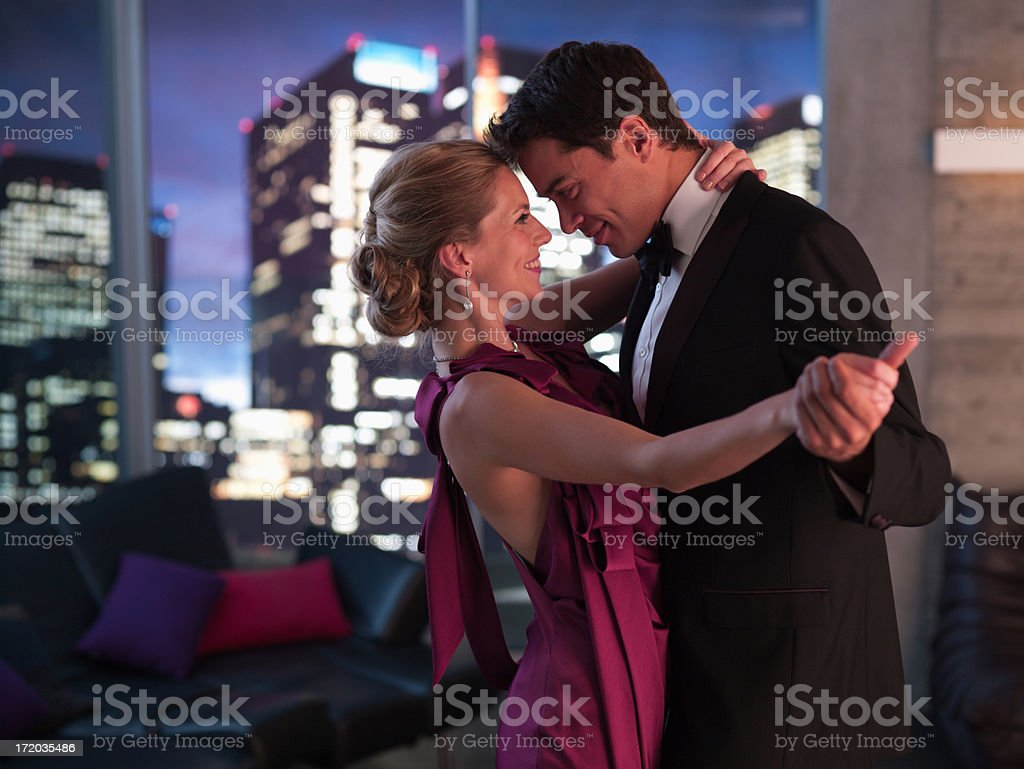 Elegant couple dancing in living room stock photo