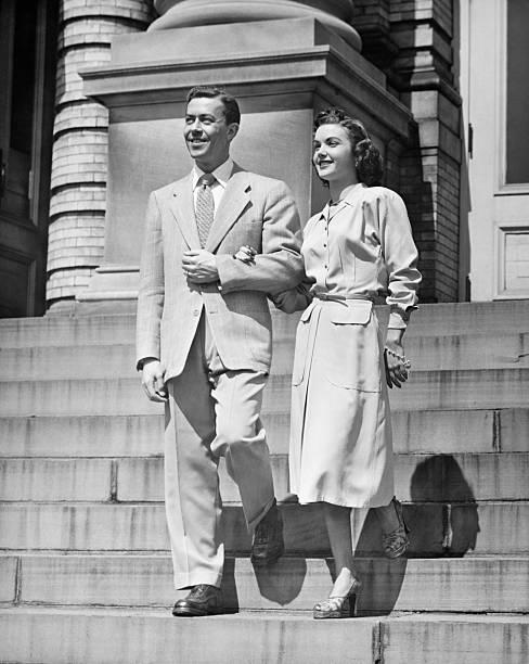 Elegant couple descending steps, (B&W) stock photo