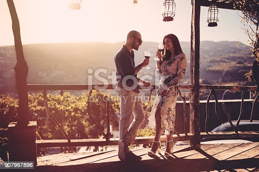 istock Elegant couple drinking red wine at French rustic vineyard winery 907967896