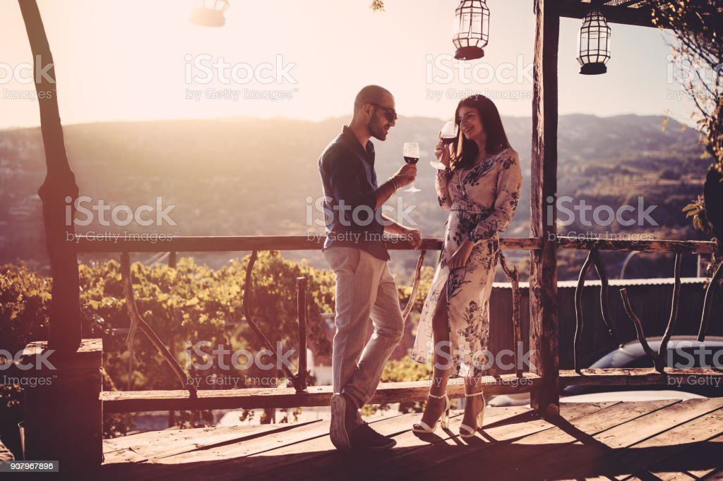 Elegant couple drinking red wine at French rustic vineyard winery stock photo