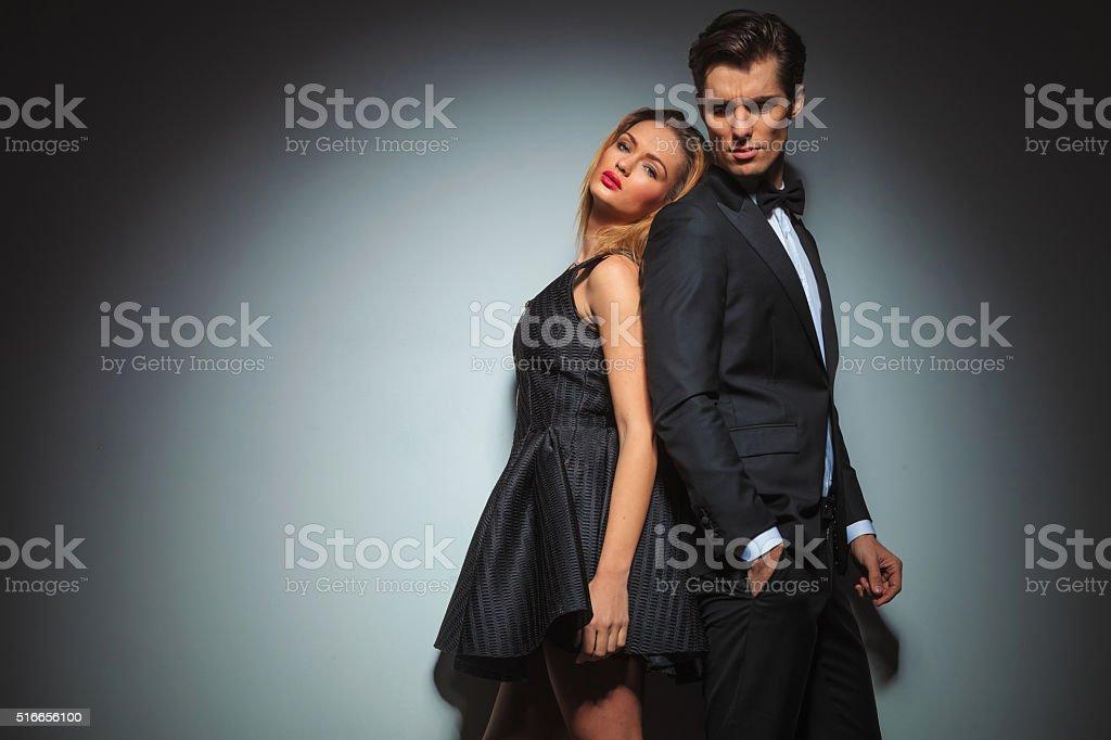 elegant couple in black posing back to back stock photo