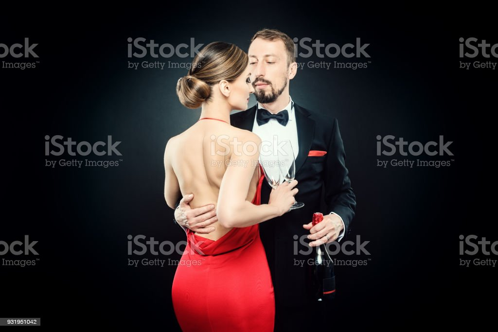 Elegant couple in evening dress embracing each other in love stock photo