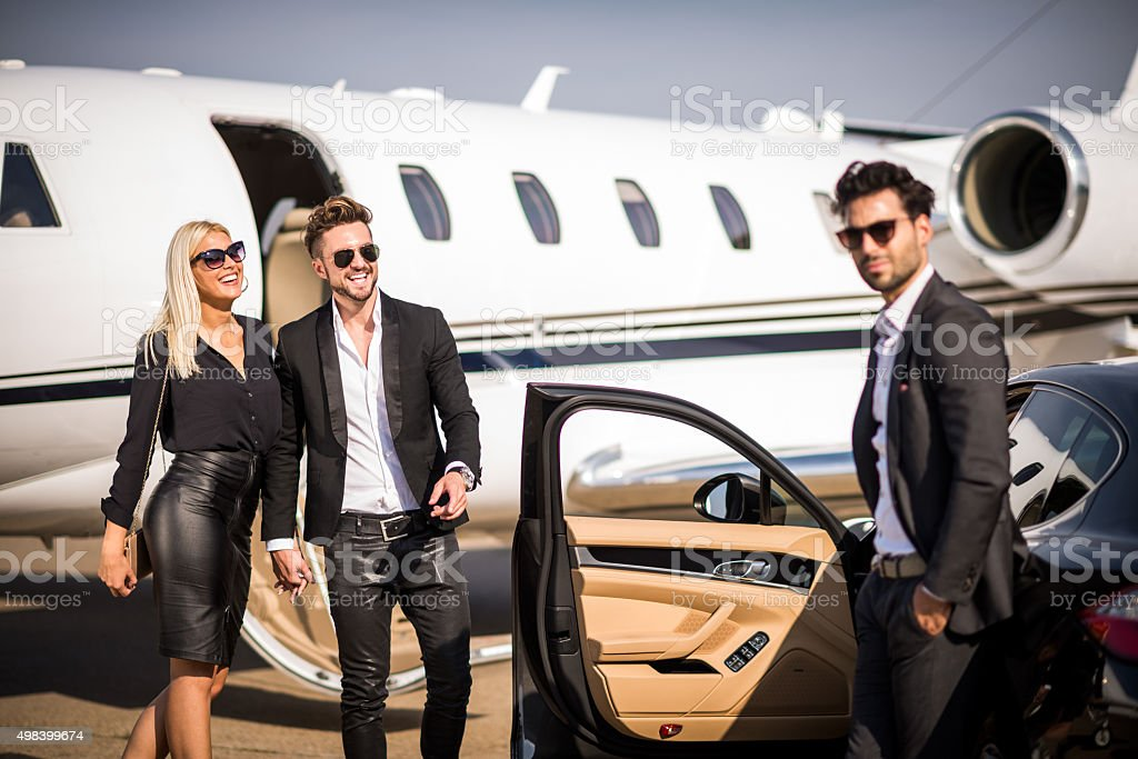 Elegant couple leaving private aeroplane stock photo