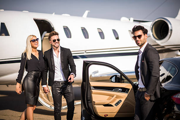 Elegant couple leaving private aeroplane stock photo