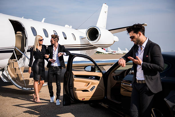 Elegant couple leaving private airplane stock photo