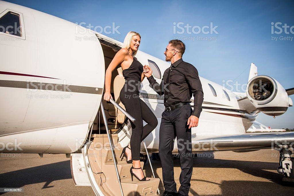 Elegant couple leaving private jet aeroplane stock photo