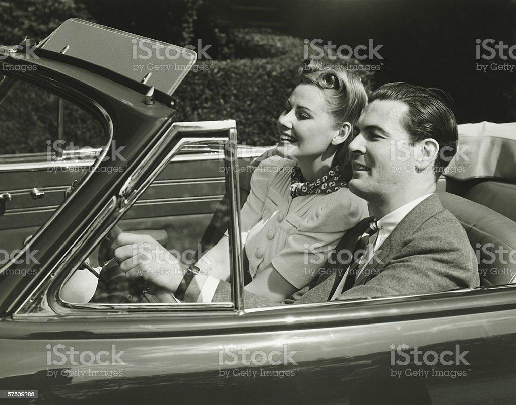 Elegant couple riding in in convertible car, (B&W) stock photo