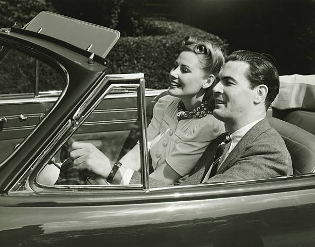elegant couple riding in in convertible car, (b&w) - 1940s style stock photos and pictures