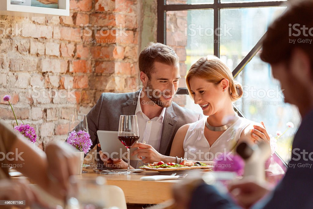 Elegant couple using a digital tablet in the restaurant stock photo