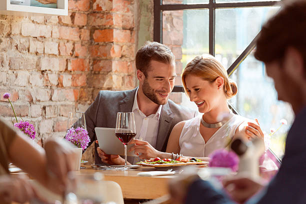elegante par usando una tableta digital en el restaurante - cena romantica fotografías e imágenes de stock
