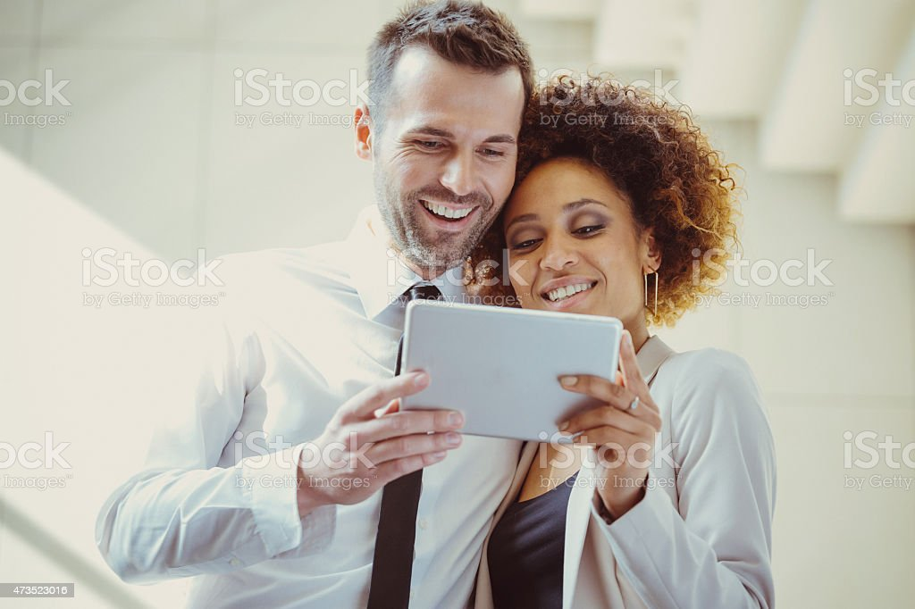 Elegant couple using a digital tablet together Happy afro american woman and caucasian man in formal outfits standing against white wall and stairs and using a digital tablet together. 2015 Stock Photo