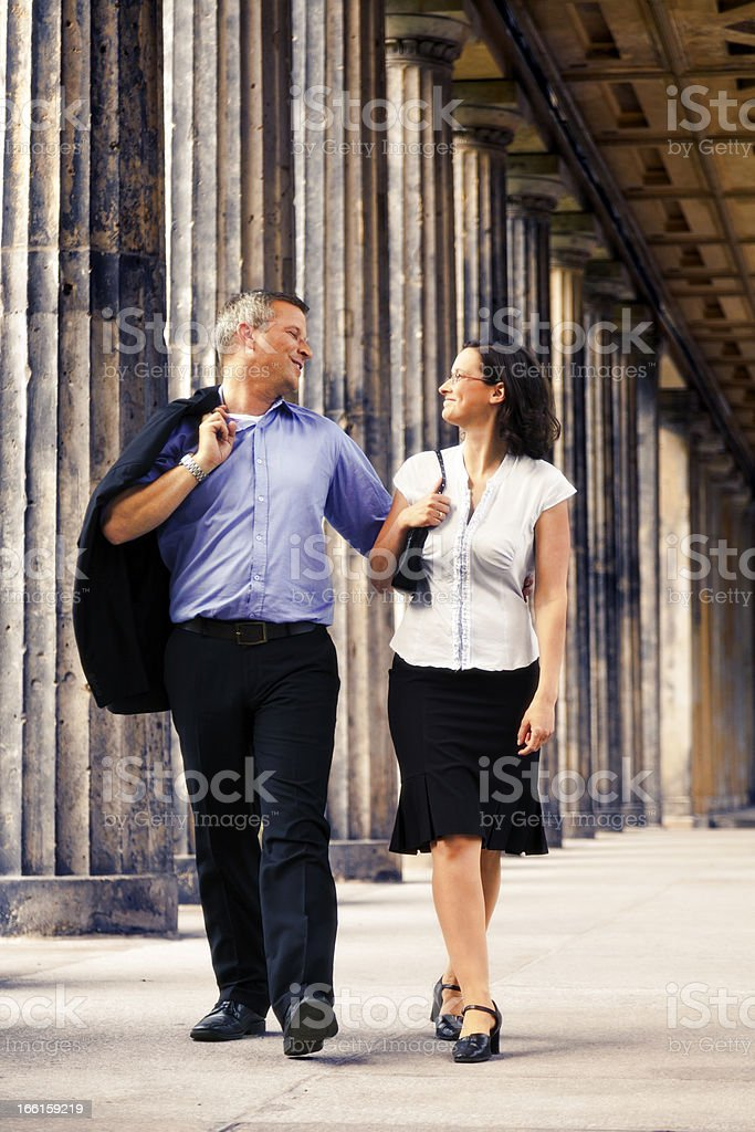 Elegant Couple Walking in Columns Passage royalty-free stock photo