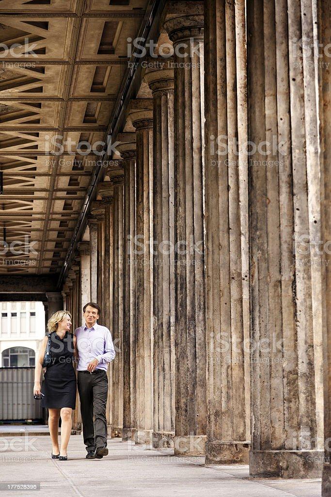 Elegant Couple Walking in Columns Passage royalty-free stock photo