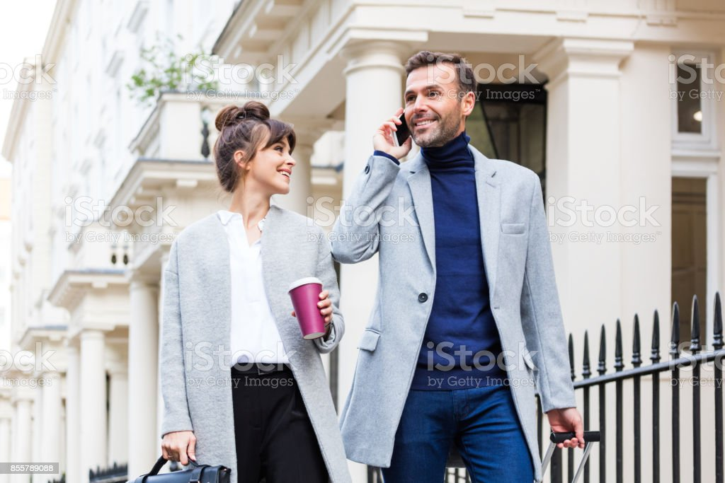 Elegant couple walking in the city street, man talking on phone stock photo