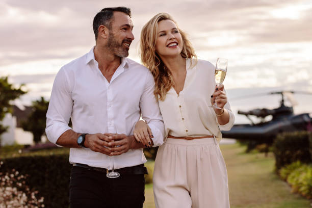 Elegant couple walking outdoors with wine Handsome man with his beautiful girlfriend walking together outdoors. Beautiful couple walking outdoors with a helicopter at the back. high society stock pictures, royalty-free photos & images