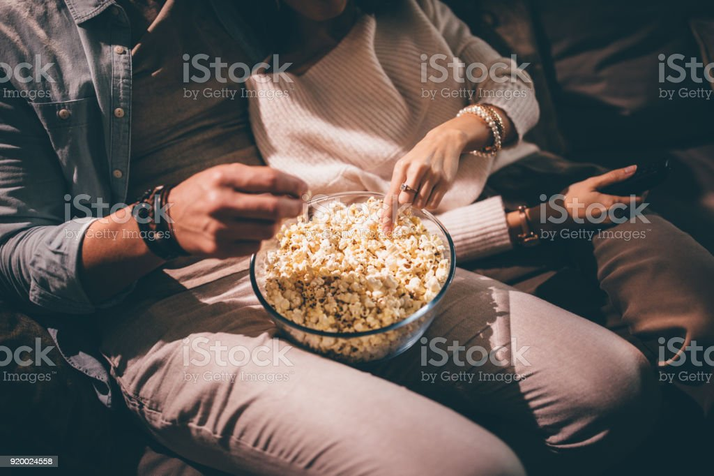 Elegant couple watching movie together and eating popcorn stock photo