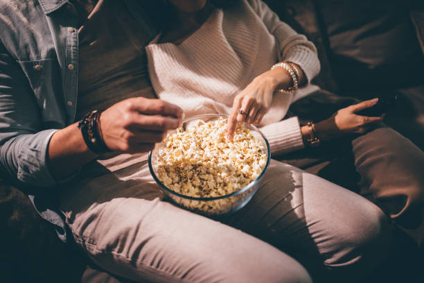 Elegant couple watching movie together and eating popcorn Close-up of chic couple's hands watching television and eating popcorn at night wundervisuals stock pictures, royalty-free photos & images