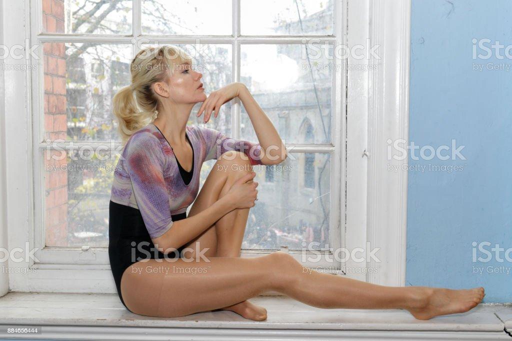 Elegant Danish ballerina full length profile seated in old window London stock photo