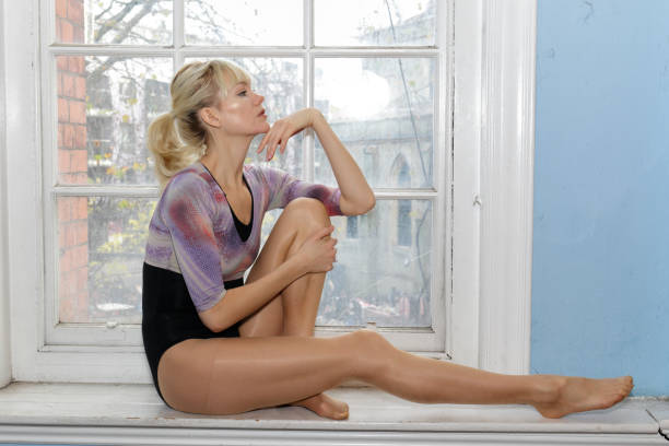 elegant danish ballerina full length profile seated in old window london - whiteway danish stock photos and pictures