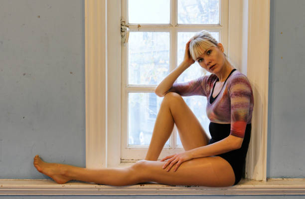 elegant danish ballerina full length sitting in old window london - whiteway danish stock photos and pictures