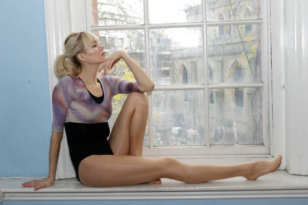 elegant danish ballerina sitting full length profile in old window london - whiteway danish stock photos and pictures