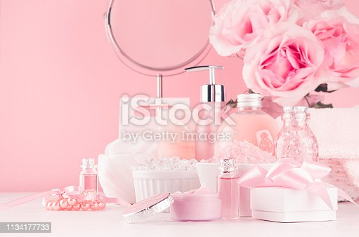 1056636898 istock photo Elegant decor for romantic girlish dressing table - different bath, spa cosmetics, accessories, roses bouquet, round mirror in pastel pink color on white wood board. 1134177733