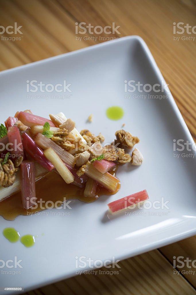 Elegant dessert - cheesecake, granola, rhubard and herb topping stock photo