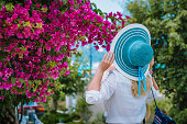 Elegant dressed woman with hat smelling beautiful colorful flowers on the islands of Greece during summer time. Romantic Traveling vacation concept.
