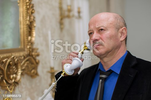 Elegant elderly man with a retro phone