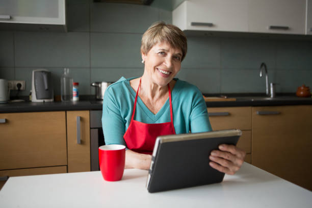 Elegant elderly woman using  tablet in the kitchen stock photo