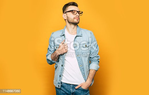 649754038 istock photo Elegant, fashion and stylish photo of handsome confident man in jeans and glasses. Guy is posing in studio 1148667050