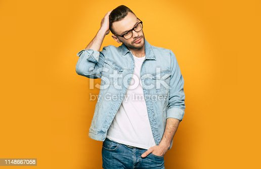 649754038 istock photo Elegant, fashion and stylish photo of handsome confident man in jeans and glasses. Guy is posing in studio 1148667058